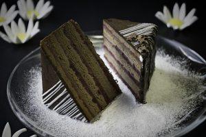 Baron kocka  Sočne kakao biskvit kore, čokoladni fil, kuvani  fil od maline, dekorisan prelivenom čokoladom.