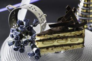 Kinder torta  Dve hrskave kore od lešnika premazane eurokremom, čokoladnim i vanil  filom uz dodatak celih komada plazma keksa, dekorisano prelivenom čokoladom.